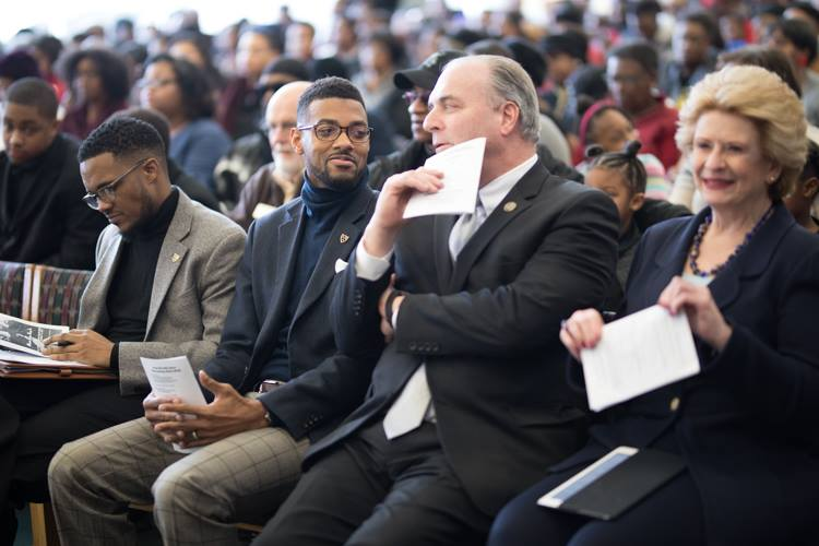 Isaiah Oliver sits along side U.S. Rep. Dan Kildee and U.S. Sen. Debbie Stabenow at the Flint Public Library MLK Day celebration.