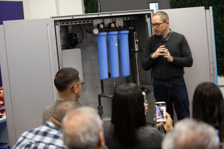 Jaron Rothkop, 501cThree's head engineer, explains the four-step filtration system of the Water Box to residents at the Latinx Technology and Community Center on Monday, Dec. 2.