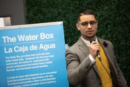 Asa Zucarro, executive director of the Latinx Technology and Community Center on Lewis Street, speaks to a crowd at a public showing of The Water Box on Monday, December 2.