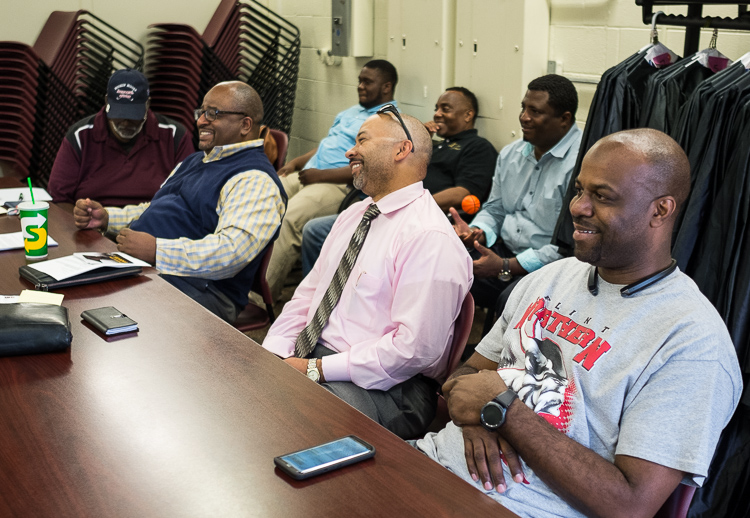 Adult advisors including Robert Matthews (left in blue vest) and 67th District Court Judge David Guinn (front, center) observe the young men of the Alpha Esquires from the back of the room during a meeting earlier this month at the Mott Community Col