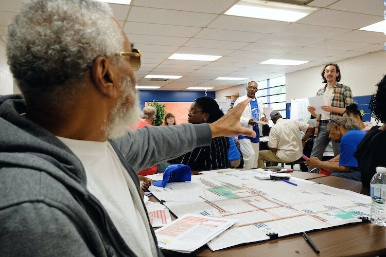 Civic Park resident Arthur Port, 77, raises a concern about overgrown corner lots to City of Flint urban designer Michael Lawlor at a Neighborhood Planning Workshop.