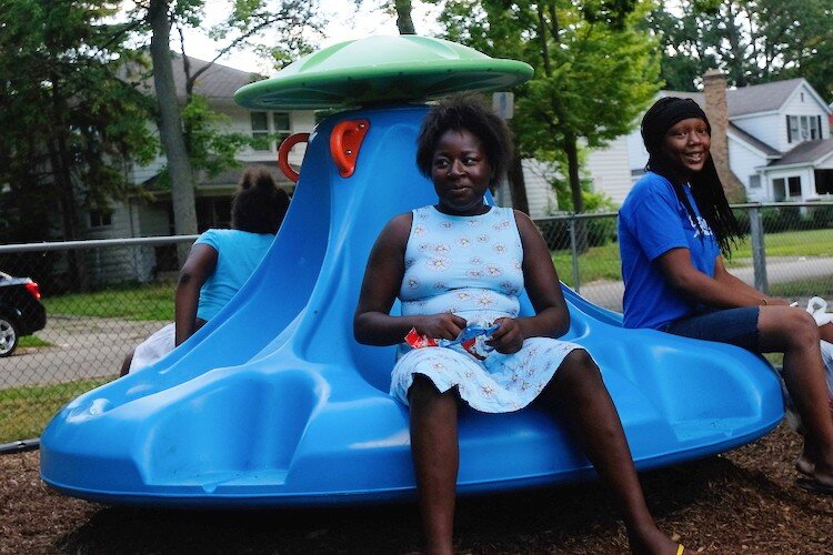 Civic Park residents Ceterra Williams (middle), Mariah Fisher (right), and Natalia Williams enjoy the spin of the new Bassett Park merry-go-round.