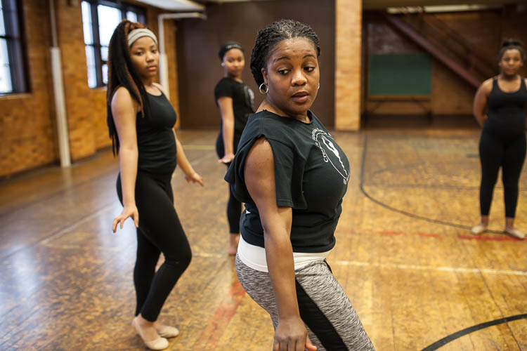 Instructor Jamise Wash-Lang demonstrates part of a routine to her Creative Expressions Dance Studio students at Berston Field House in Flint. The dancer at left is Janiyah Fells, 12, of Flint.