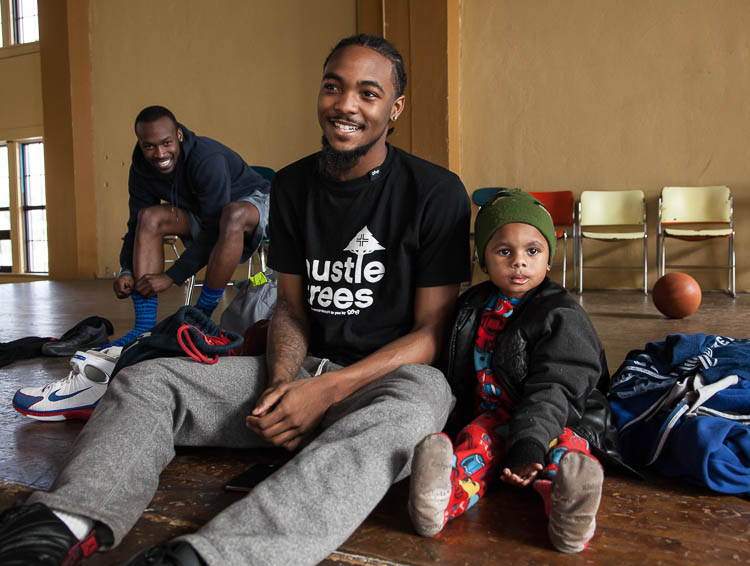 D.J. Dye, 3, of Flint sits with Simeun McGee, 21, of Flint on the stage in the gym at Berston Field House in Flint. D.J. was there with his father Troy George, 23, of Flint who was in the basketball game at that moment. At left is Quavon Trawick.