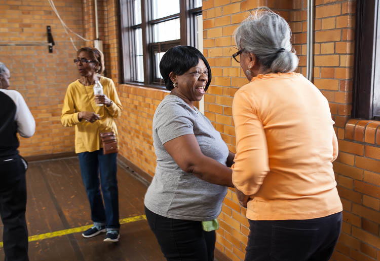 Phyllis Abrams of Flint (center) spends a moment socializing with Carolyn Jackson of Flint during a break in their line dancing class in the small gym at Berston Field House in Flint.