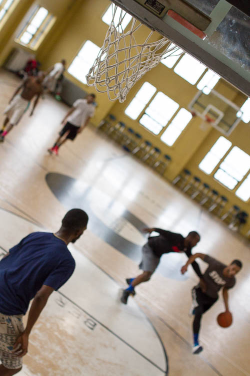 Young men, mostly in their 20s, play basketball at Berston Field House in Flint.