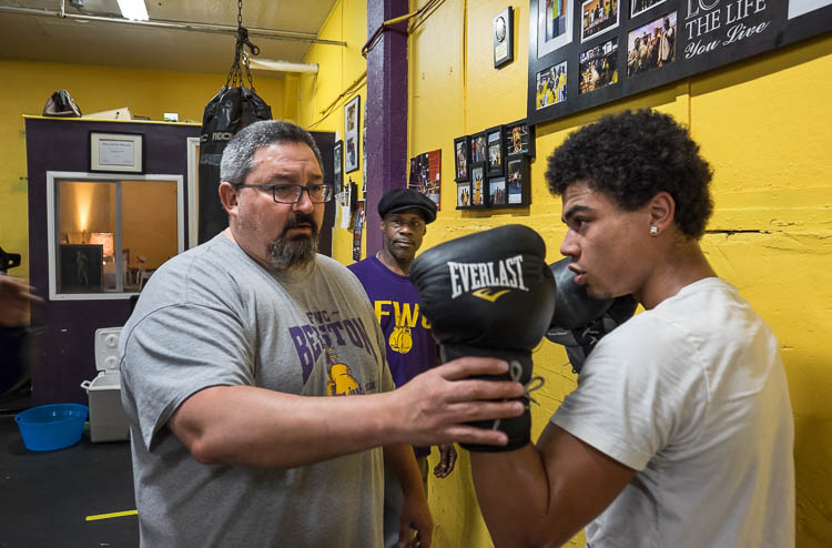 Berston boxing coach Steve Ayala of Ortonville works with Seth Woodbury, 18, of Swartz Creek, on his form in the boxing gym at Berston. Woodbury has been training at Berston for just a few weeks. Coach Paul LeSears looks on in background.