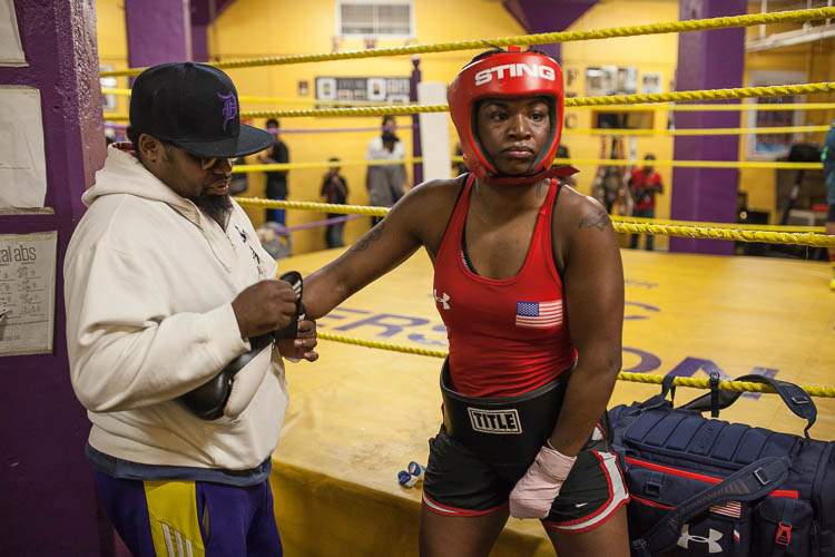 Boxing coach Jason Crutchfield helps Claressa Shields put on her gloves in the boxing gym at Berston Field House in Flint.