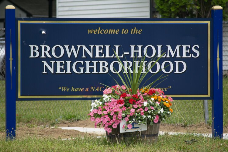 The Brownell-Holmes welcome sign stands on the corner of Home and Oxley. In front of it sits one of the many flower baskets that lines the neighborhood's streets.