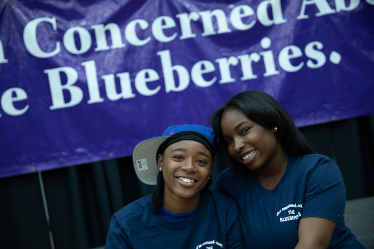 Blueberry Ambassadors pose in front of a recreation of the billboard sign that started the Blueberry Movement in 2013.