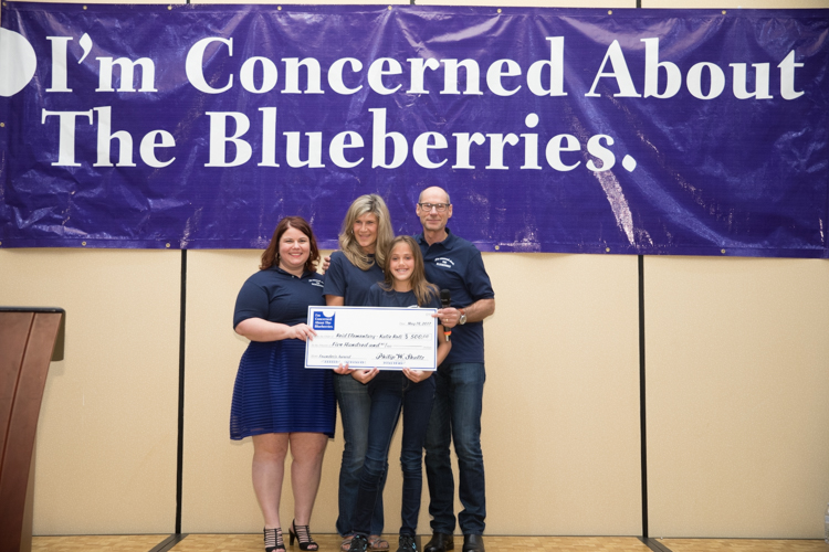 Marjory Raymer, teacher Kristie Philpott, 2017 Founder's Award winner Katie Roti, and Blueberry Founder Phil Shaltz, pose for a photo. Shaltz makes a donation to the school to honor Katie's Blueberry Moment.
