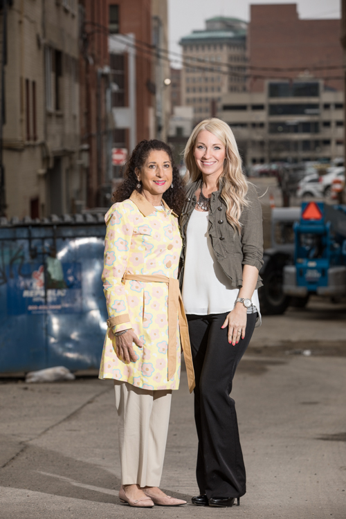 Kathleen Gazall (left) and Kristy Bearse, both members of the Friends of the Alley Committee, pose in Brush Alley—at the heart of new downtown investment. A 30-day, $50,000 fundraising campaign to string lights in the alley kicks off on Monday, April