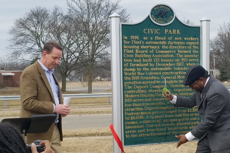 Flint City Councilman Maurice Davis cuts the ribbon at the official rededication ceremony for the Civic Park Neighborhoods historic marker.