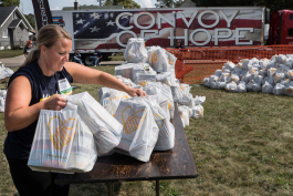 Tara Stimson of Davison Twp. organizes bags of groceries at the Convoy of Hope event in 2017