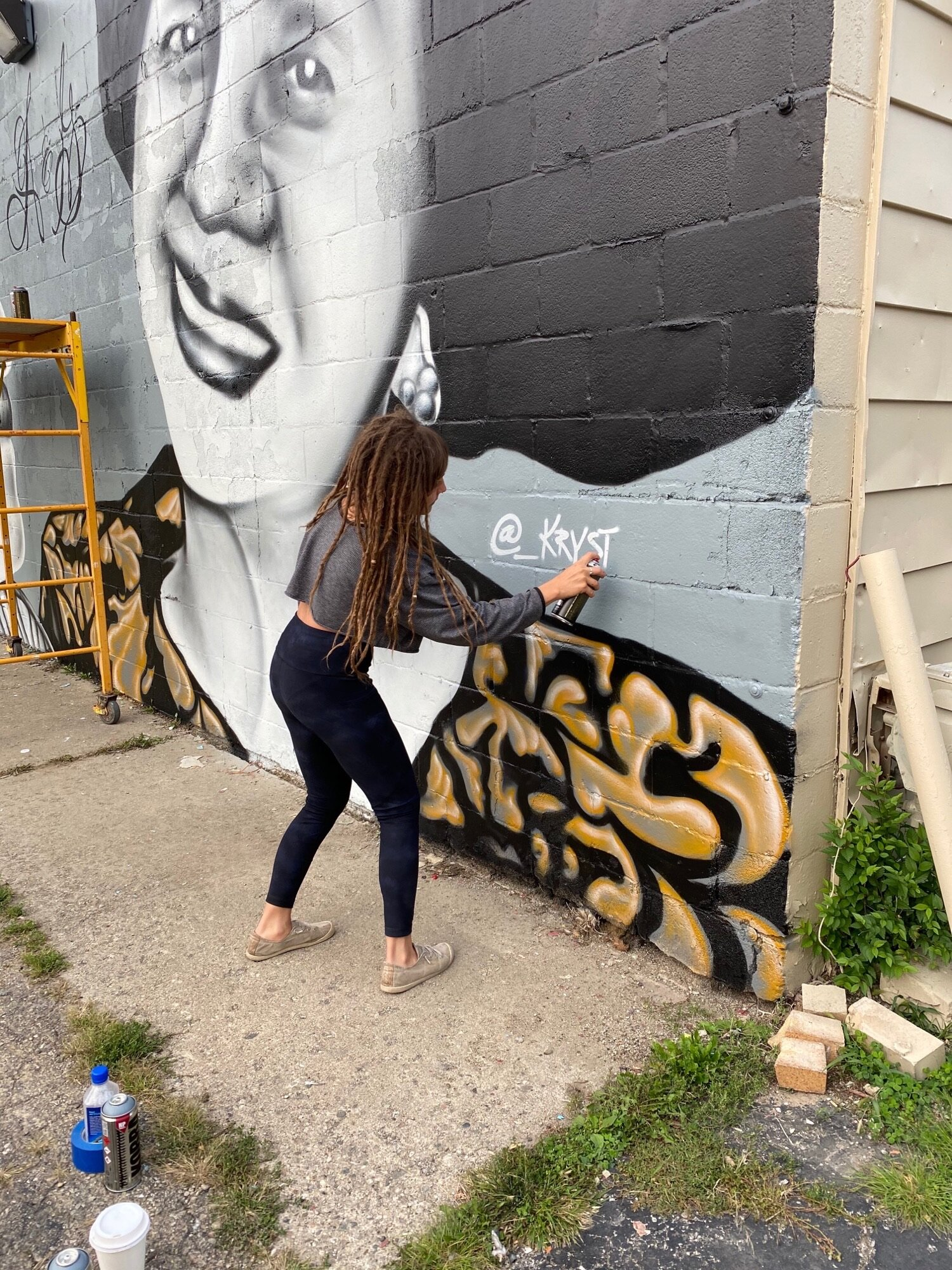 Local artist Krystal Cooke signing her completed mural of Mom and Pops.
