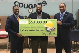 LeeRoy Wells Jr., vice president of operations support for Consumers Energy; Glenn WIlson, president and CEO Communities First Inc.; and Kyle McCree, community affairs area manager for Consumers pose with a check that will fund the Coolidge Community