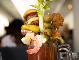 The Loaded Bloody Mary includes cheeseburger slider on a homemade brioche roll, bacon, sweet potato waffle fries, shrimp, roasted jalapeno, asparagus, chicken nuggets, pickle and olives—all atop Cork's homemade mix.