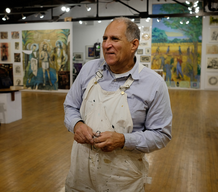 Mark Davidek, son of artist Stefan Davidek gives a tour of his father's work at the exhibit at Buckham Gallery in Flint.