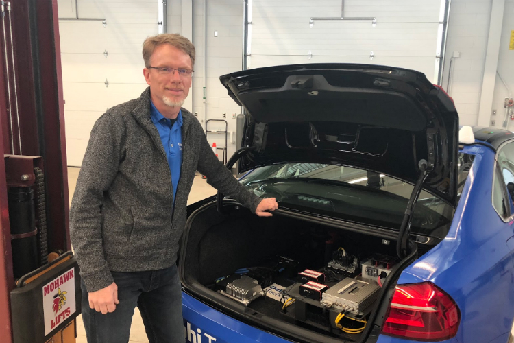 Keith Confer, engineering manager of Advanced Vehicle Systems for Delphi, stands next to an Intelligent Drive  system prototype at Kettering University's GM Mobility Research Center.
