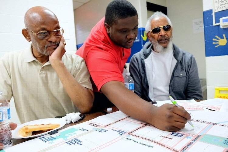 City of Flint Neighborhood Planner Dequan Allen leads a focus group beside Civic Park residents Ernest-C Martin, 72 (left) and Arthur Port, 77, (right) on September 7 for the neighborhood planning workshop.