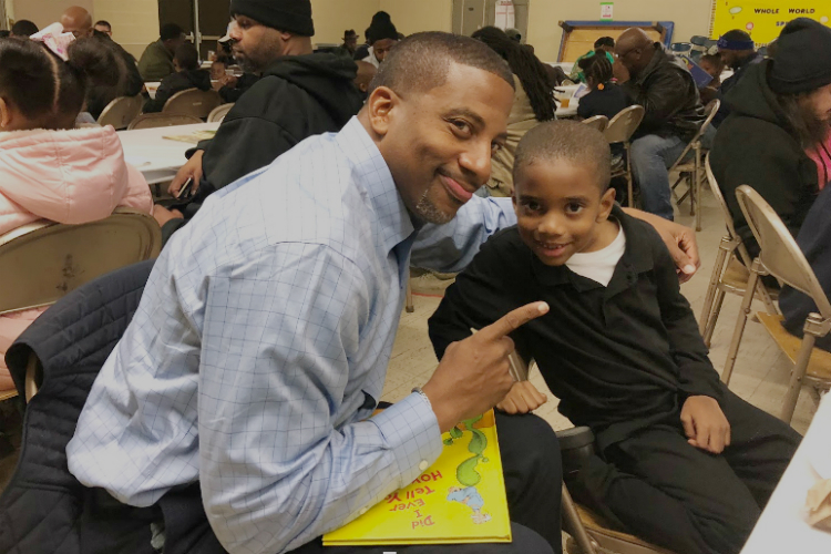 Derrick Munson poses with his son Brandon, 6, during Donuts with Dad at Durant-Tuuri-Mott Elementary School in Flint.