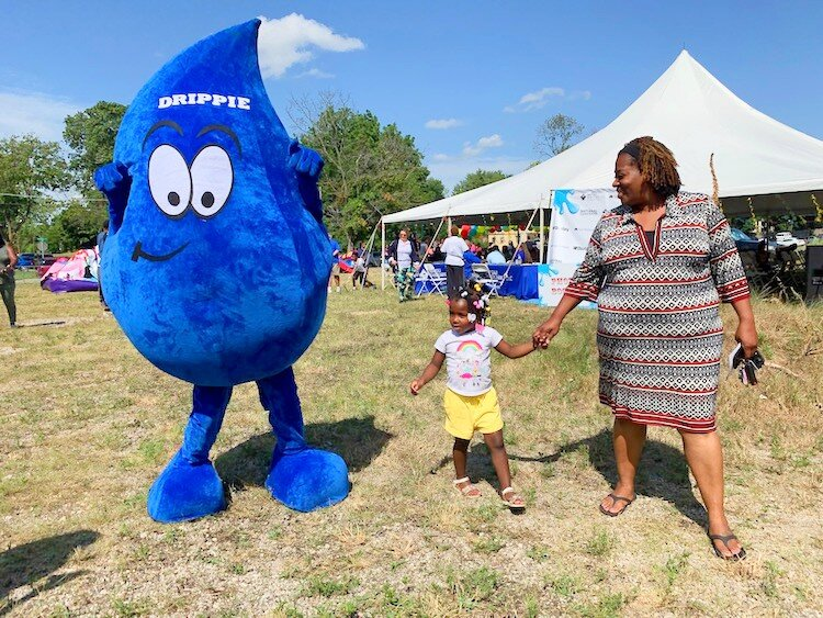 "Ruth Harrison with her granddaughter Sarai Mitchell, 3 walking alongside Drippie the mascot at the 2nd Flint Town ""Back to School"" Carnival Splash."