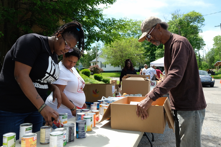 Prior to the V2xV grand opening, volunteers distributed food to neighborhood residents.