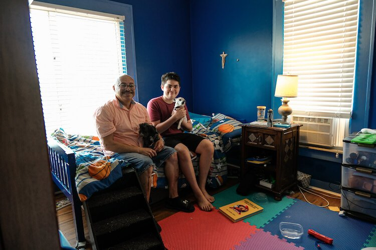 Ricky Reyes, 61, sits in his childhood bedroom that now belongs to his grandson Enrique Reyes (seated on the right).