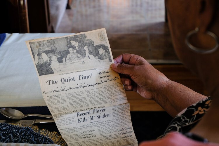 Raynetta holds a 1961 Detroit Free Press education article showing the Speed family in their dining room during an evening after school.