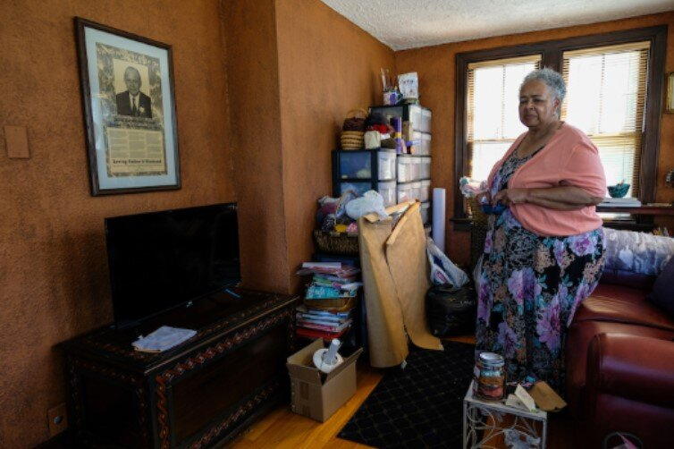 "Raynetta Speed, 69, stands in her childhood music room where she took piano lessons. It's now her knitting room and also the place where her father's memorial, ""In Remembrance of John R. Speed"" hangs (pictured left)."