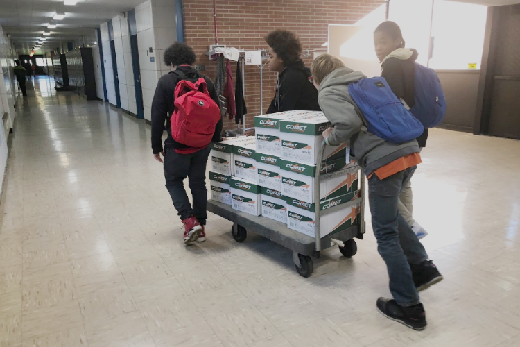 Scott Middle School students push a delivery of supplies gifted through the Flint Classroom Supply Fund through the newly reopened school.
