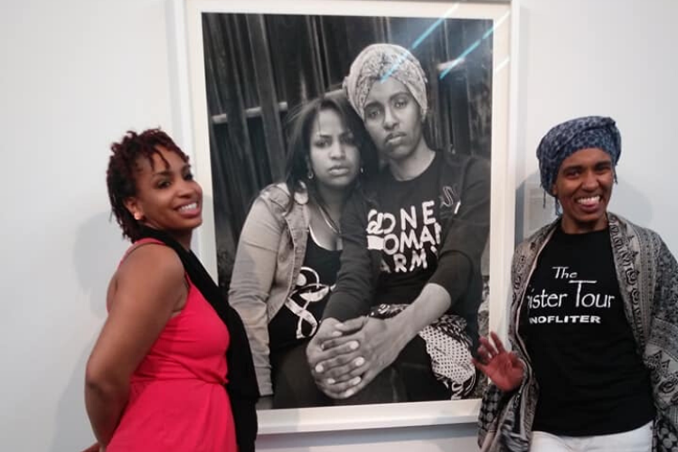 Shea Cobb and Amber Hasan stand next to their portrait on display at Gavin Brown's Enterprise in New York.