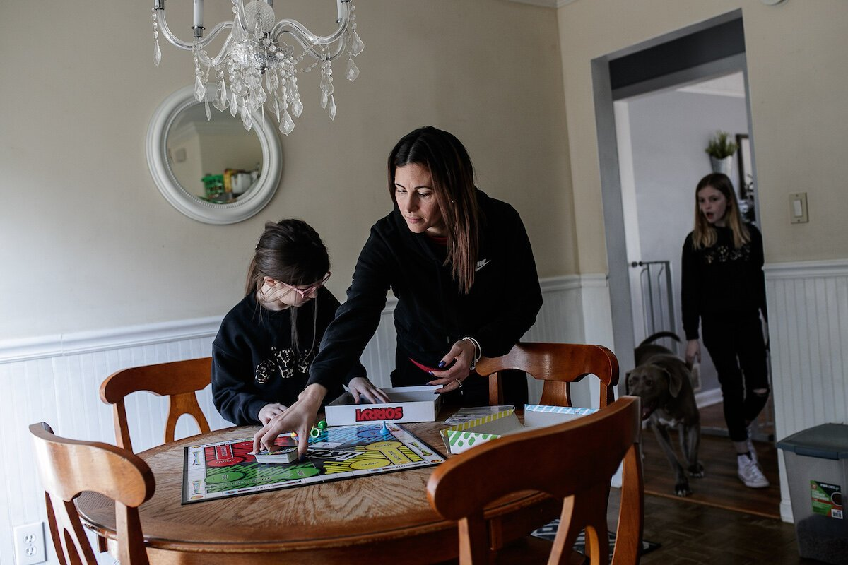 Giselle, Yuliette and Lily Parks set up a board game to play together at home.