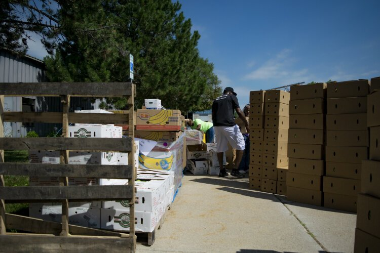 Boxes and pallets line the sidewalk of the Hasselbring Senior Center parking lot.