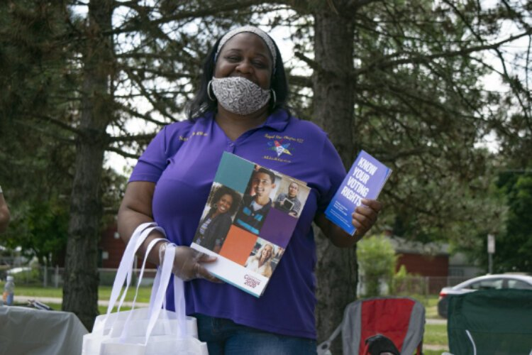 Holly Wilson from the Neighborhood Engagement Hub holds up reading material being handed out to all community members who attended the drive-thru event.