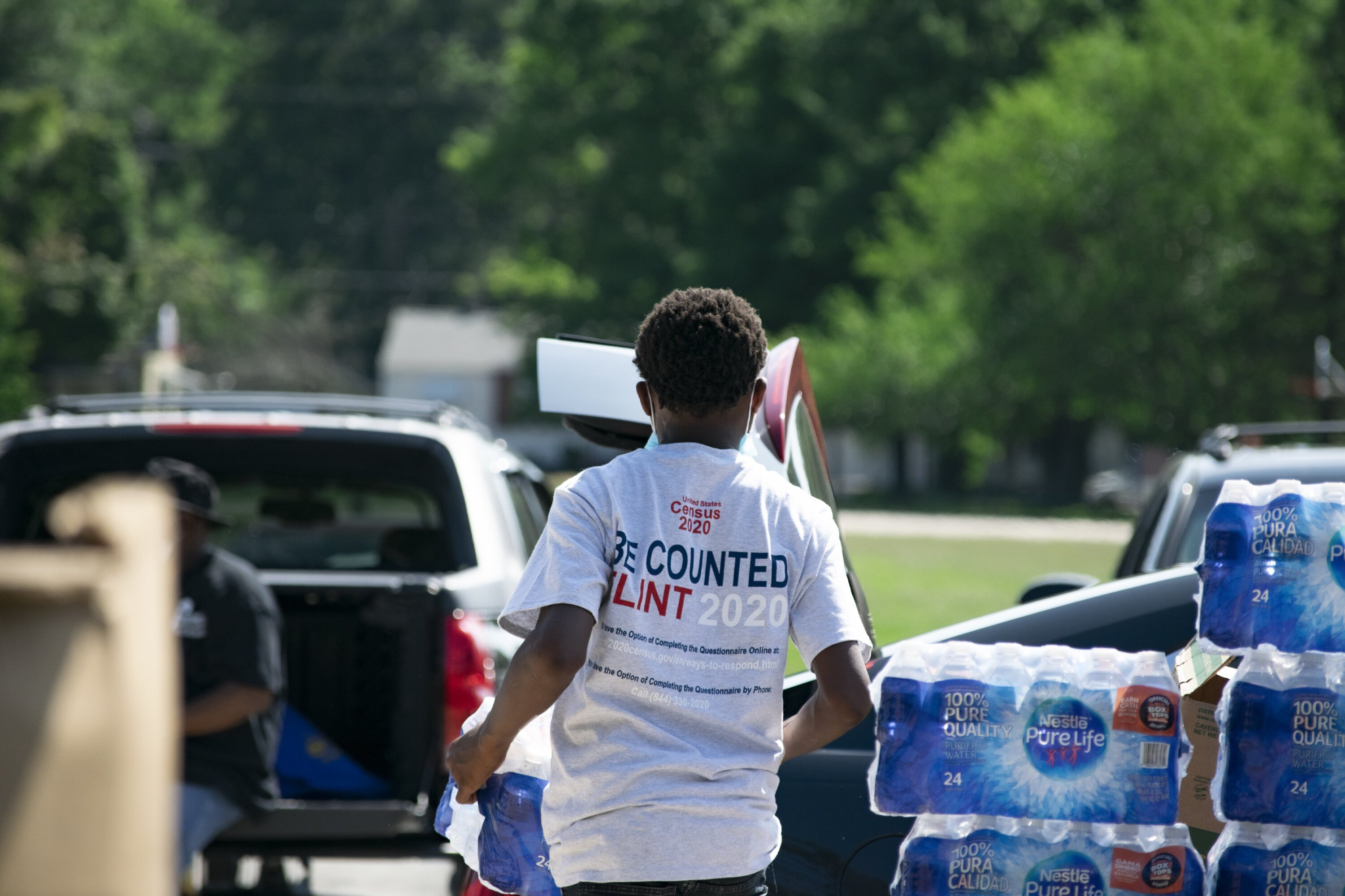 A young volunteer hands out packs of bottled water to community members.