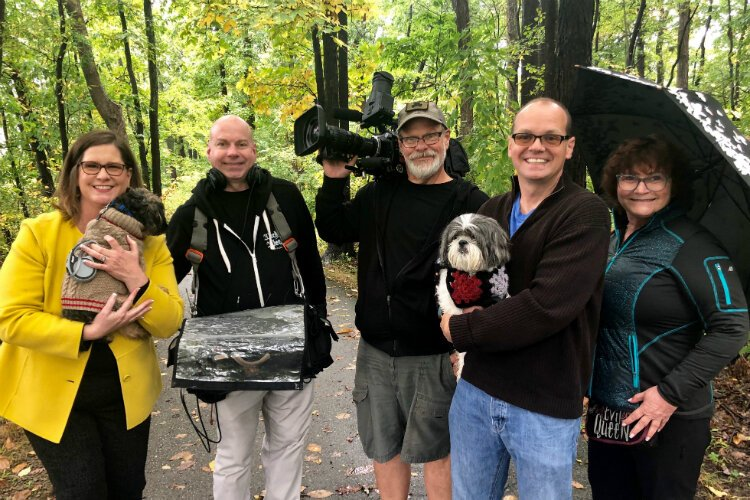 Katie Bach (left) and her husband, Matt, (second from right) pose with the film crew from 'House Hunters' and their two dogs Chewie and Chester.