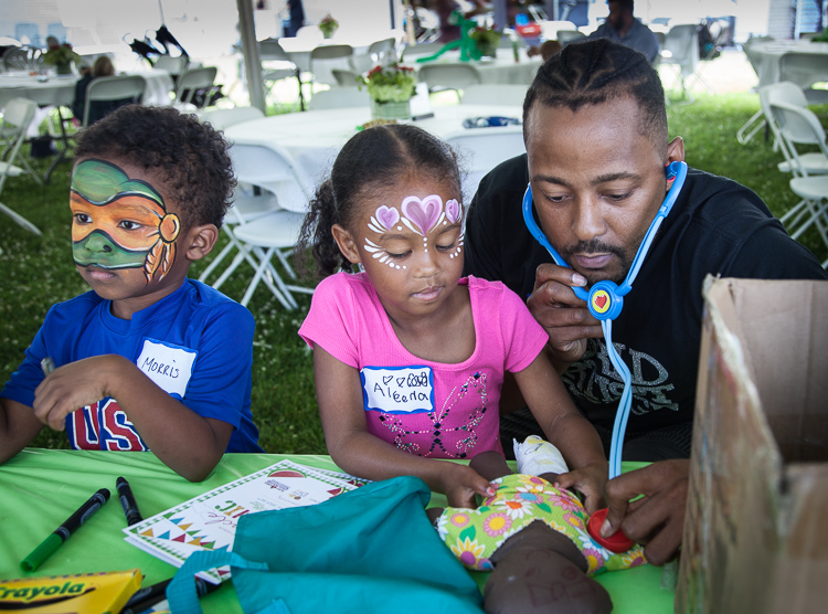 Former MSU basketball standout and Flintstone Morris Peterson plays with his son Morris III (left) and daughter Aleena at the 8th Annual Miracle Picnic at the Sloan Museum on Tuesday.