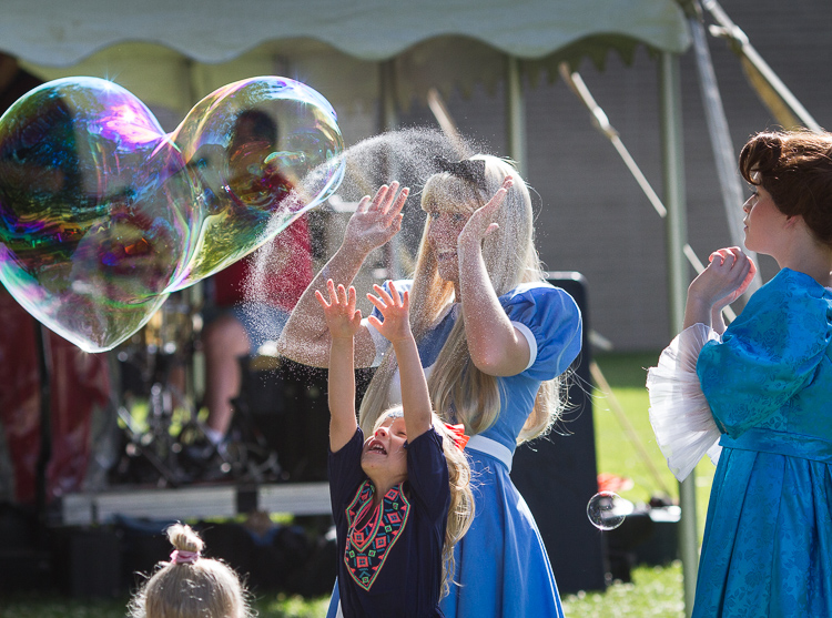 "Ashley Grovesteen as ""Alice"" and Elizabeth Timm (right) as ""Wendy Darling"" react as a child bursts a bubble at the 8th Annual Miracle Picnic at the Sloan Museum."