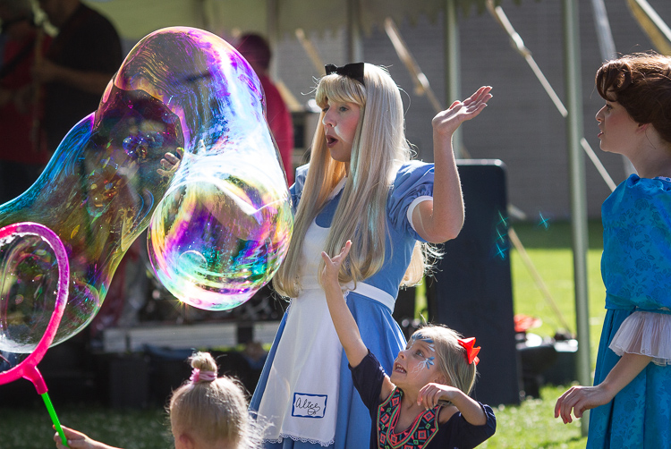 "A child reaches to burst a bubble at the 8th Annual Miracle Picnic at the Sloan Museum on Tuesday.  Ashley Grovesteen as ""Alice"" and Elizabeth Timm (right) as ""Wendy Darling"" play with the children just before the bubble bursts."