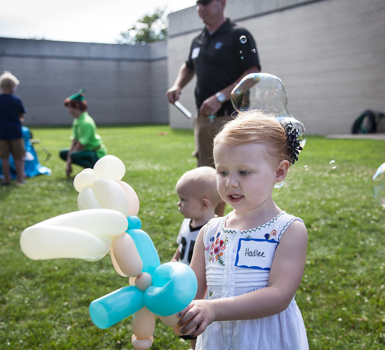 Hadlee Deines, 3, plays with a balloon sculpture at 8th annual Miracle Picnic for Hurley Children's Hospital at the Sloan Museum on Tuesday. She underwent treatment for leukemia at Hurley.