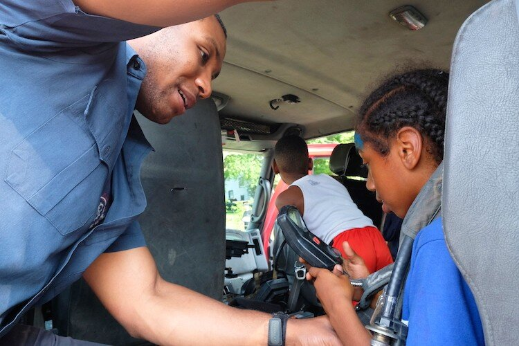 Firefighter Daryl Jones shows Jamire Thomas, 8 the smoke mask inside the firetruck at the Civc Park Art Parade.