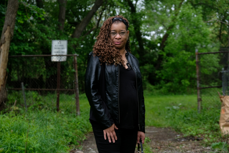 Linn Aikins stands at the entrance to Dougherty Park, which she has made her mission to cleanup.