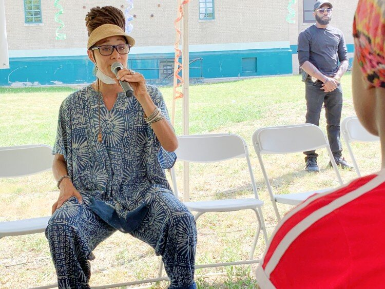 "Mama Sol performing her piece ""Hard to Swallow"" under a tent at the Flint Town ""Back to School"" Carnival Splash."