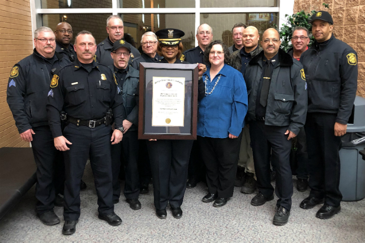 Mott Community College's Public Safety officers pose withTheresa Stephens-Lock with their accreditation award.