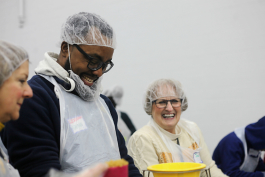 10.	Lenwood Hayman jokes along with fellow volunteer Jana Blagg who works at the Grand Blanc West Middle School pantry.