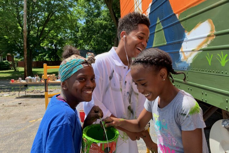 Aniyah Colston, 13; Isaiah Crockett, 16; and Aniyah Colston (left to right) giggle before the camera while painting a mural on the water distribution trailer in the Joy Tabernacle parking lot.