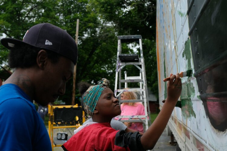 Aniyah Colston, 13, focuses on her measured strokes on the water distribution trailer mural.