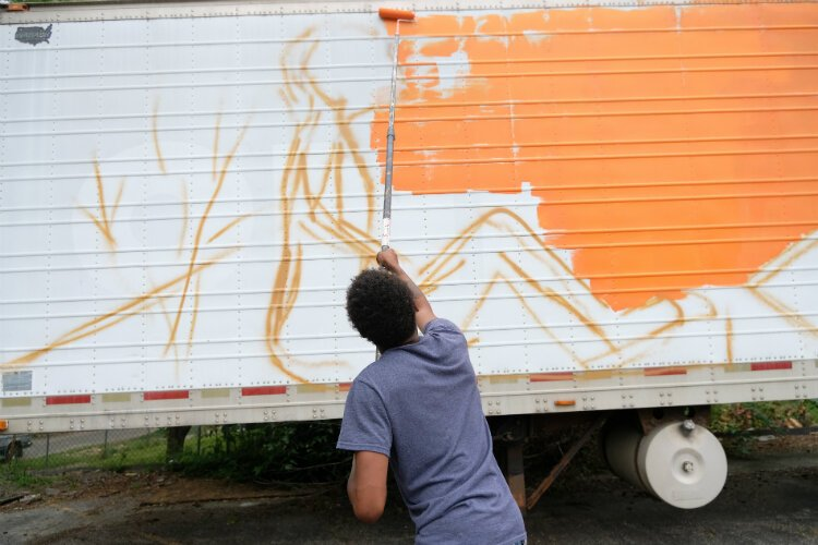 Cedreon Chapman, 16, applys an orange back drop to the water distribution trailer mural during a Friday morning paint session.