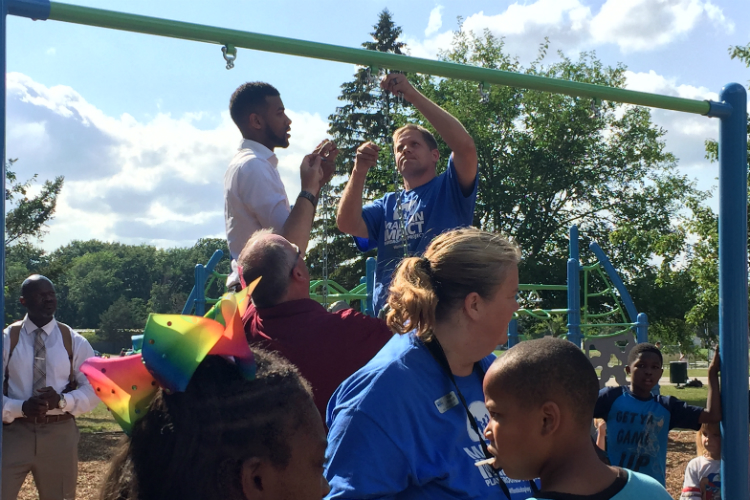 Isaiah Oliver, president of the Community Foundation of Greater Flint, (standing left) at the new playground opened Tuesday at Hasselbring Senior Center.